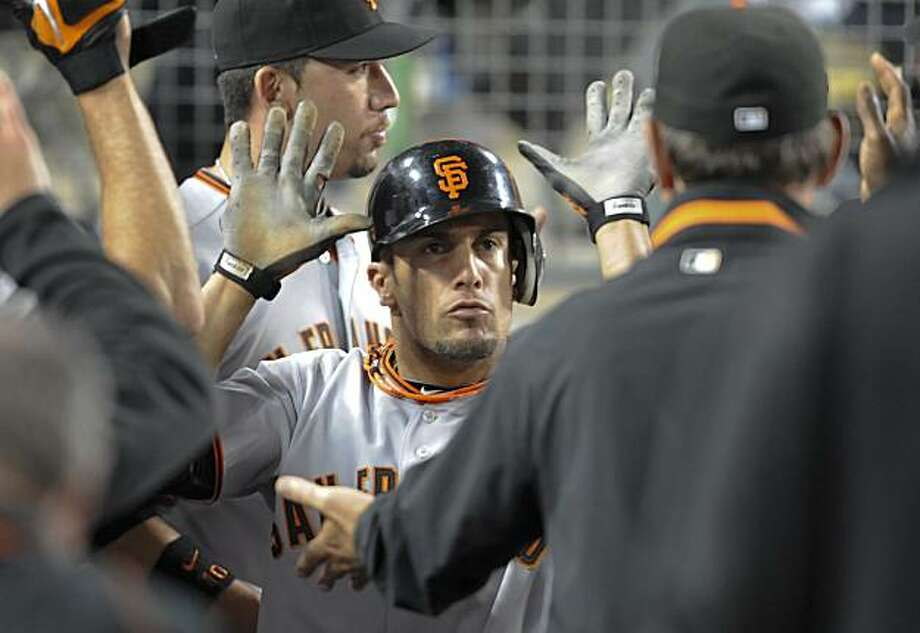 San Francisco Giants center fielder Andres Torres celebrates with his team in the dugout after scoring in the ninth inning of a baseball game against the Los Angeles Dodgers, Tuesday, July 20, 2010, in Los Angeles. The Gaints won 7-5. Photo: Gus Ruelas, AP