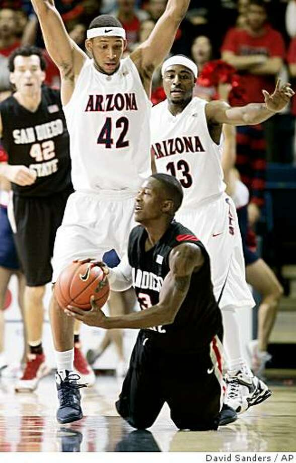 San Diego State's Richie Williams (3) looks for help as he is on his knees as Arizona's defenders Jamelle Horne (42) and Nic Wise (13) apply defense the first half of an NCAA college basketball game, Wednesday, Dec, 10, 2008 in Tucson, Ariz. (AP Photo/Arizona Daily Star, David Sanders) **  MANDATORY CREDIT, NO MAGS, NO SALES ** Photo: David Sanders, AP