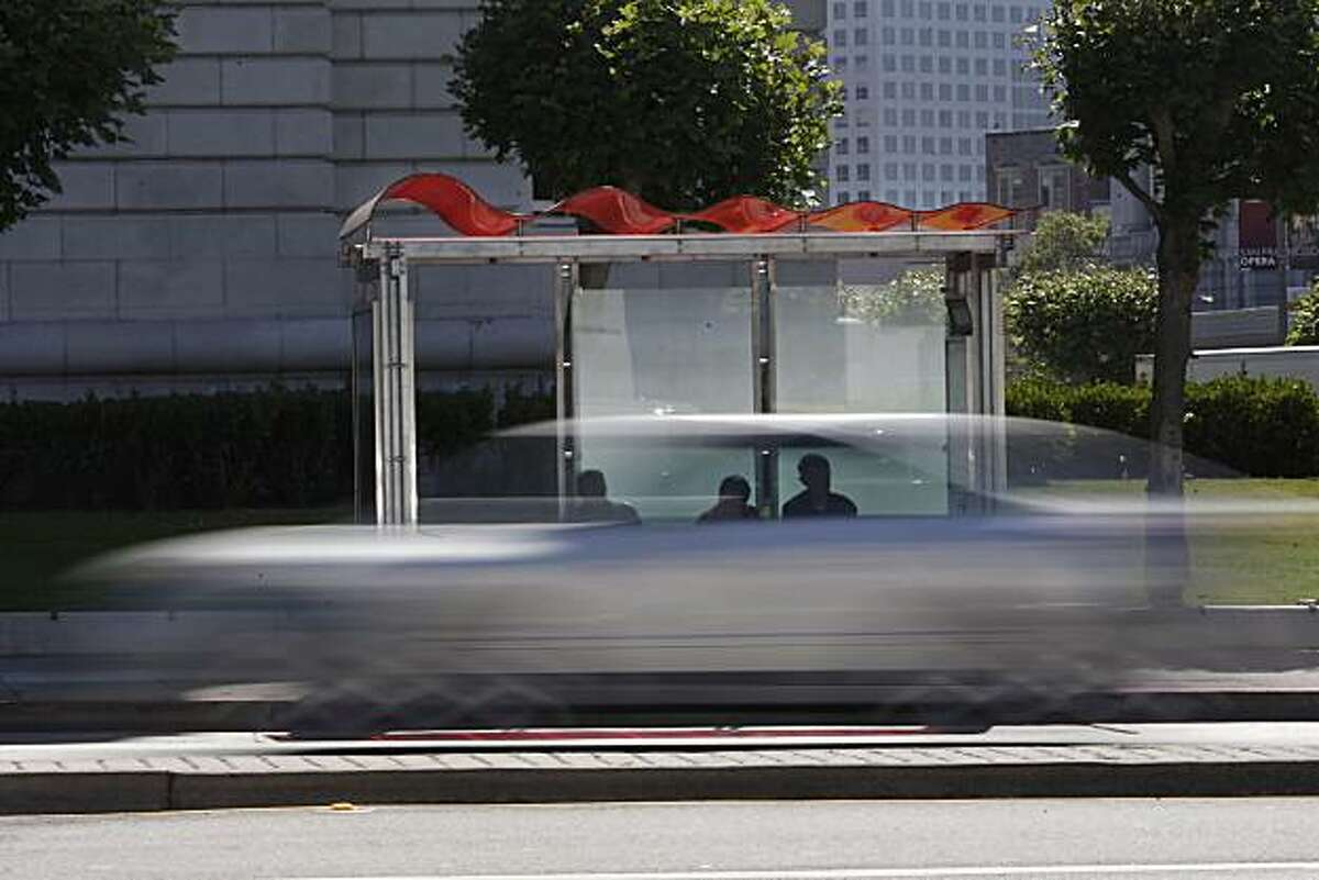 People wait for a bus at a bus shelter with a new roof as traffic passes by on Van Ness Avenue in San Francisco, Calif. on Wednesday July 14, 2010.