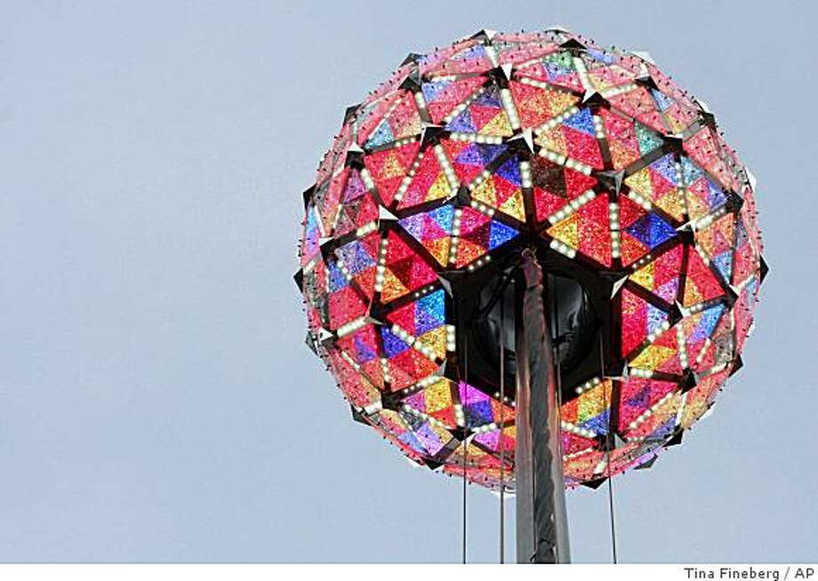 The new Times Square New Year's Eve ball is seen lit up as it moves along the flagpole on the roof of One Times Square in New York during the annual test of the ball, Sunday, Dec. 30, 2007.  The new ball is more than twice as bright as the old one with enhanced color capabilities and energy-efficient LED lights. This year is the 100th anniversary of the New Year's Eve ball drop in New York Times Square.  (AP Photo/Tina Fineberg) Photo: Tina Fineberg, AP
