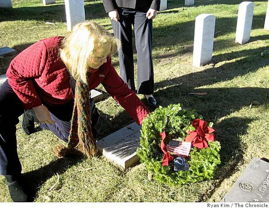 Joyce Lively, a member of the San Francisco chapter of the Daughters of the Revolution, lays a wreath at a grave in the San Francisco National Cemetery at the Presidio. Photo: Ryan Kim, The Chronicle
