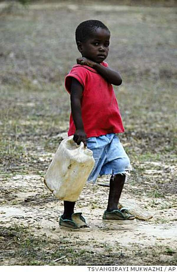 A young boy carries a container to fetch water in Mutare, about 220 km east of Harare, Zimbabwe Friday Dec. 5, 2008. South Africa is sending more military doctors to its northern border to treat Zimbabwean cholera victims, underlining fears of a regional disease outbreak linked to Zimbabwe's collapse. Cholera is easily prevented and cured, but Zimbabwe's medical and water-treatment systems have all but disappeared. The disaster has led to renewed calls, on Friday from the United States among others, on longtime, increasingly autocratic Zimbabwean leader Robert Mugabe to step down. (AP Photo/Tsvangirayi Mukwazhi) Photo: TSVANGIRAYI MUKWAZHI, AP