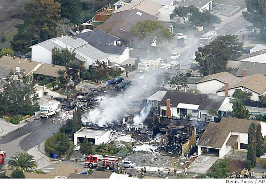 **RETRANSMISSION FOR ALTERNATE CROP**Smoke rises from a fire after an F-18 military jet crashed into a suburban neighborhood in San Diego on Monday, Dec. 8, 2008. An F-18 military jet approaching Marine Corps Air Station Miramar crashed near a busy highway in a densely populated San Diego neighborhood Monday, causing at least one house fire.  (AP Photo/Denis Poroy) Photo: Denis Poroy, AP