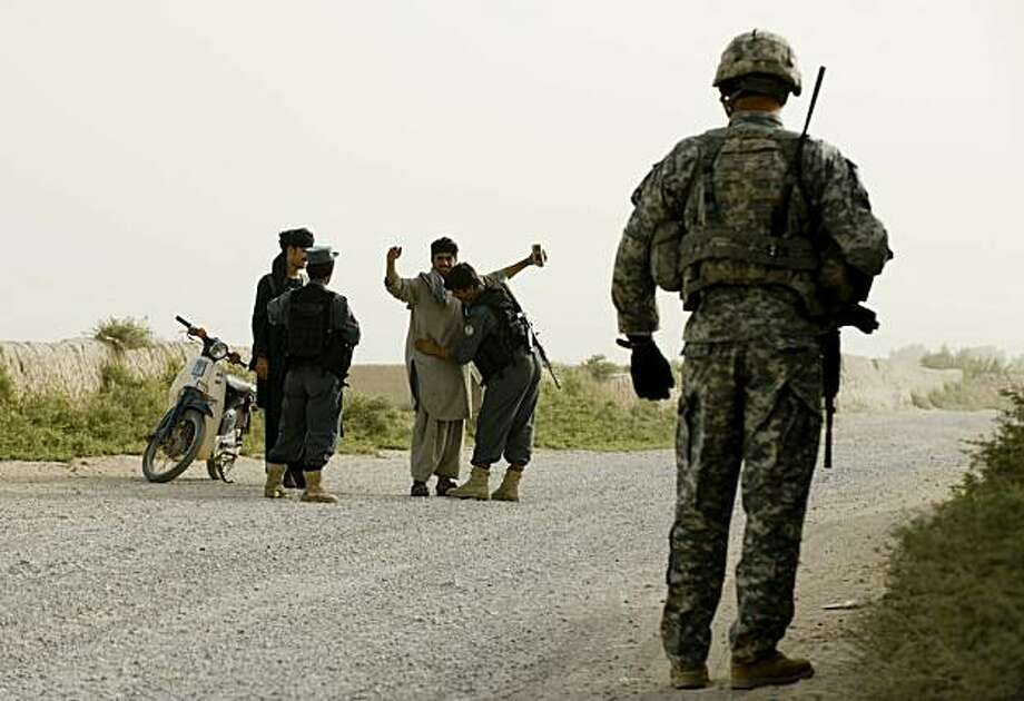 Two Afghan National Police stop and frisk Afghan men travelling on a scooter during a patrol by US soldiers of First Squadron, 71st Cavalry in Dand district of Kandahar Province in Afghanistan on July 21, 2010. NATO and the United States have 143,000 troops in Afghanistan, set to peak at 150,000 in coming weeks as they take a US-led counter-insurgency to the insurgents' southern strongholds in an effort to speed up an end to the war. Photo: Manpreet Romana, AFP/Getty Images