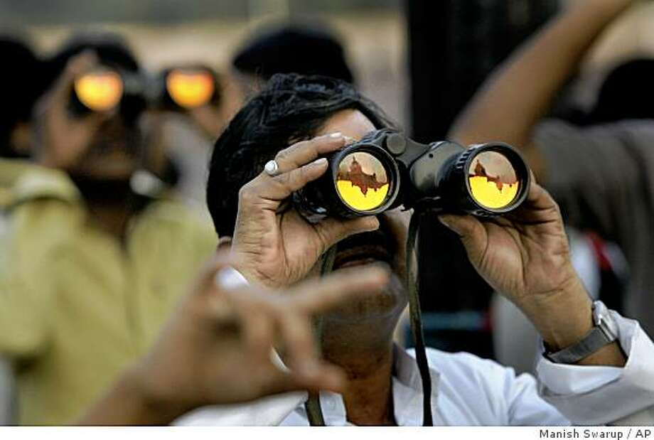 Indian tourists look at the damaged Taj Mahal hotel through binoculars in Mumbai, India, Wednesday, Dec.10, 2008. The Taj Mahal hotel is one of the two hotels which was attacked by terrorists on Nov. 26, 2008. (AP Photo/Manish Swarup) Photo: Manish Swarup, AP