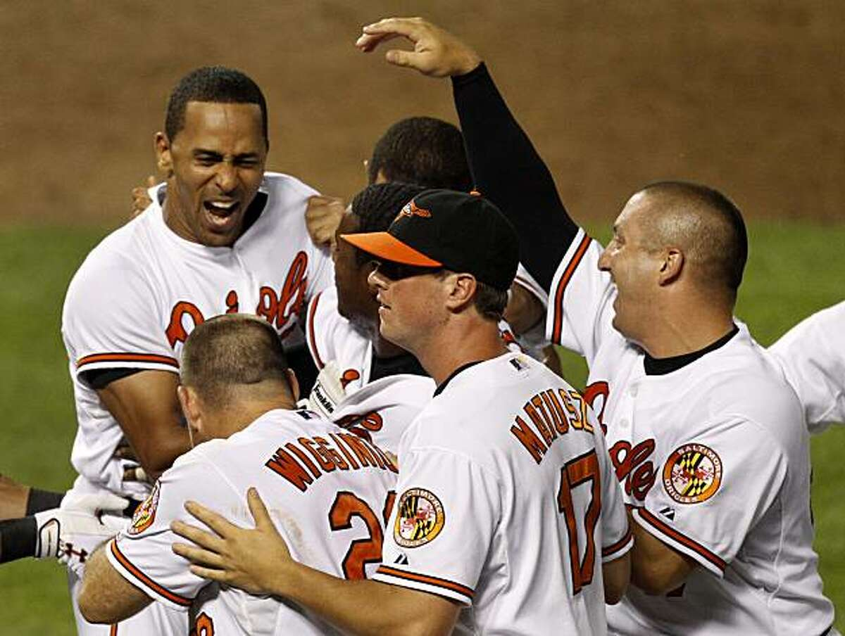 Baltimore Orioles' Julio Lugo, left, is mobbed by teammates after driving in the game winning run against the Tampa Bay Rays for a 11-10 win in the 13th inning of a baseball game, Tuesday, July 20, 2010, in Baltimore.