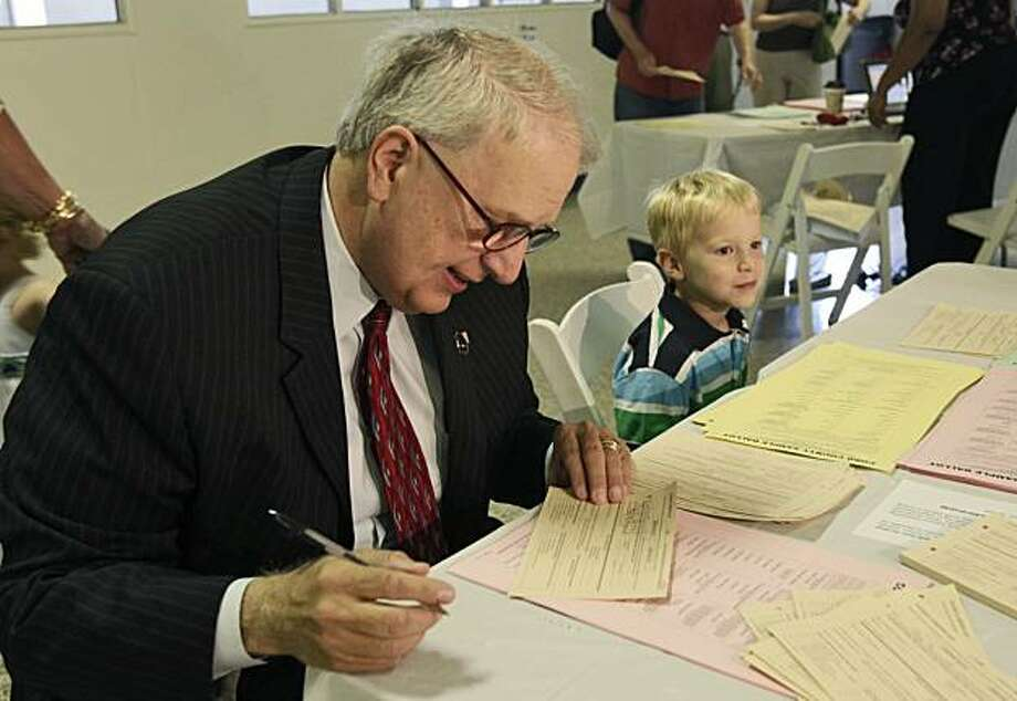 "100720 - Marietta - Former Gov. Roy Barnes fills out his voter forms with his grandson Will ""Baseball"" Barnes.  Today is Will's 6th birthday.   Will  had been to last nights Braves game, and had ""Braves"" stenciled on his arm so the Governor called him thenickname.   Former Gov. Roy Barnes votes at Marietta Middle School in Marietta.   Tues,  July 20, 2010 Photo: Bob Andres, AP"