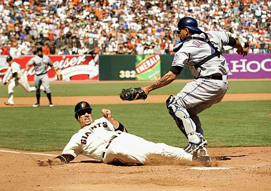 Travis Ishikawa of the San Francisco Giants slides in to home plate under the tag of New York Mets catcher Henry Blanco in the ninth inning at AT&T Park on Sunday. Ishikawa was called out on the play and the Mets went on to win 4-3 in ten innings. Photo: Ezra Shaw, Getty Images