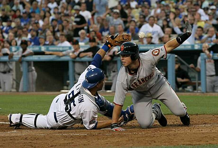 LOS ANGELES, CA - JULY 19:  Buster Posey #28 of the San Francisco Giants looks for the call after sliding safely into home with a run as catcher Russell Martin #55 of the Los Angeles Dodgers loses the ball in the third inning on July 19, 2010 at Dodger Stadium in Los Angeles, California. Photo: Stephen Dunn, Getty Images