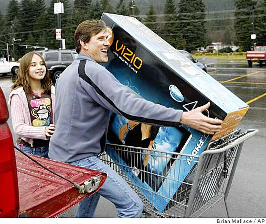Michael Mitchell smiles as he lifts his new flat screen television into his truck as his daughter Mikayla watches. Mitchell and his family were shopping Friday,Nov. 28, 2008 at the Wal-Mart Supercenter in Juneau, Alaska, taking advantage of the Black Friday sale. (AP Photo/ Brian Wallace/Juneau Empire) Photo: Brian Wallace, AP