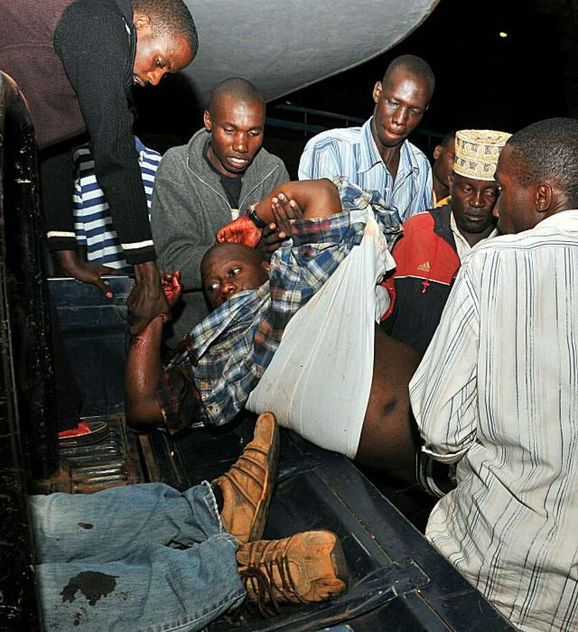 People carry an injured man in Kampala's Mulago hospital, on July 12, 2010 after twin bomb blasts tore through crowds of football fans watching the World Cup final, killing 64 people, including an American, and wounding scores others.  Somalia's Shebab insurgent group claimed responsibility for overnight bomb blasts in Kampala that left at least 74 people dead. The Al Qaeda-inspired movement's top leader had warned in an audio message earlier this month that Uganda would face retaliation for its role in supporting the western-backed Somali transitional government. Photo: Stringer, AFP/Getty Images