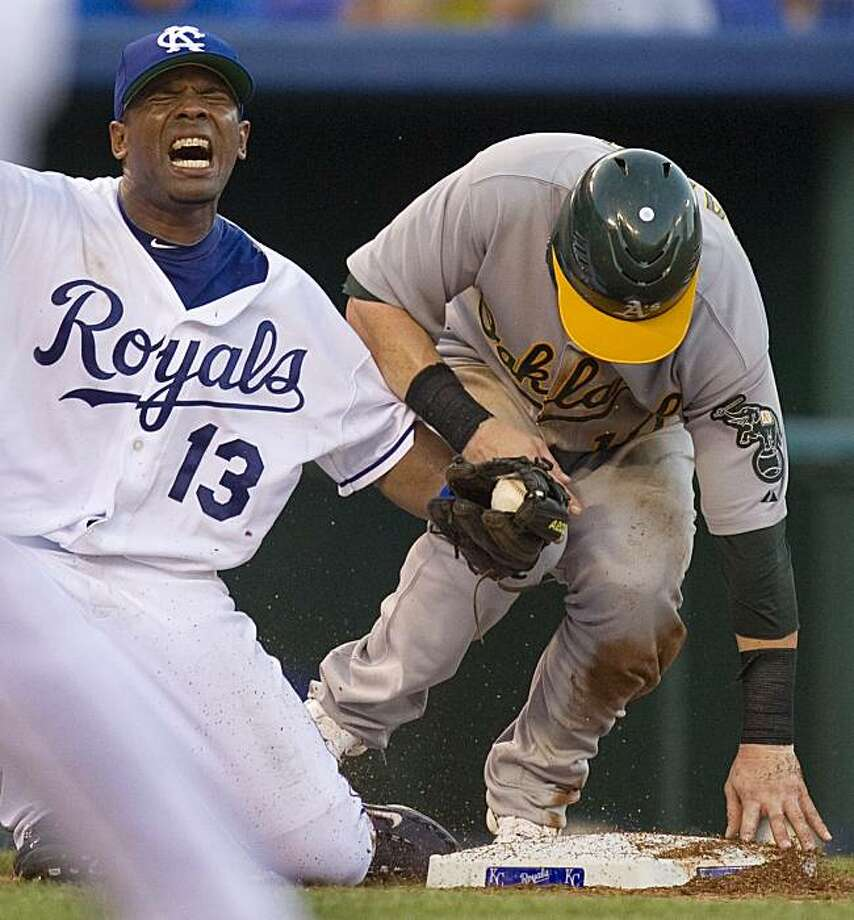 Kansas City Royals third baseman Alberto Callaspo (13) reacts after colliding with Oakland Athletics' Daric Barton as he beat the tag at third for a triple during the seventh inning of a baseball game Saturday, July 17, 2010 in Kansas City, Mo. Photo: Charlie Riedel, AP