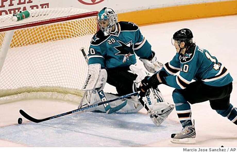 San Jose Sharks goalie Evgeni Nabokov, of Kazakhstan, (20) and defenseman Christian Ehrhoff, of Germany, watch the puck get in for a goal on a shot from Edmonton Oilers center Kyle Brodziak, not pictured, in overtime of an NHL hockey game in San Jose, Calif. on Saturday, Dec. 6, 2008. Edmonton won 3-2. (AP Photo/Marcio Jose Sanchez) Photo: Marcio Jose Sanchez, AP