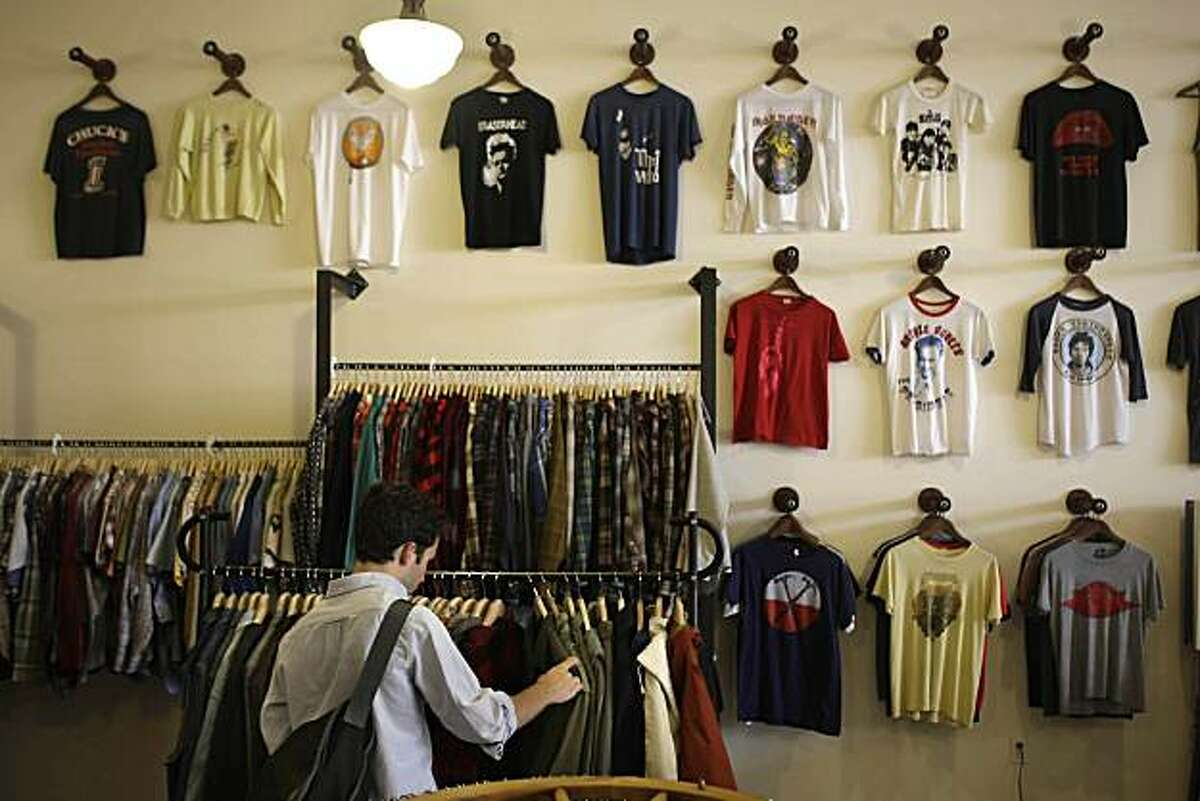 A wall of vintage T-shirts are seen on display at After Life while Julien Bracq of France looks through clothes on a rack in San Francisco, Calif. on Thursday July 8, 2010. This installment of intersection focuses on unique shops within a small radius -- in this case, inner Mission District.