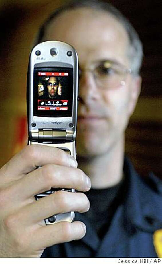 Connecticut State Police Sgt. Jim Smith of the state police cybercrimes unit poses with a cell phone in Windsor Locks, Conn.,  Thursday, May 22, 2008.  Smith conducts seminars in which he warns parents about the use of cell phones to send nude pictures.   (AP Photo/Jessica Hill) Photo: Jessica Hill, AP