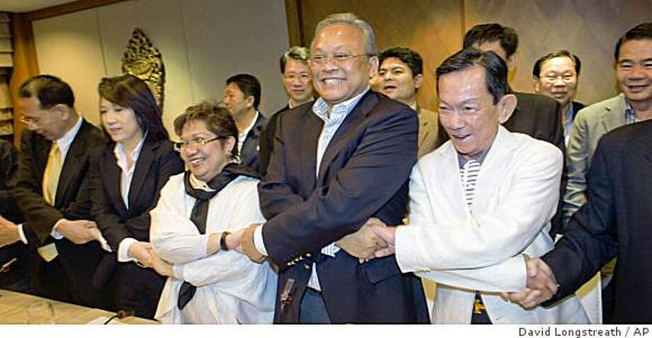 Ranongrak Suwanshawee of the Phua Phaen Din Party, center left, Democrat Party  Secretary-General Suthep Thaugsuban, center, and Sanan Kachornprasart of the Chart Thai Pattana Party, center right, along with other Thai members of Parliament celebrate Saturday, Dec. 6, 2008, in Bangkok, Thailand, after announcing it had enough support to form a new government following a six-month political crisis that has paralyzed the country.  (AP Photo/David Longstreath) Photo: David Longstreath, AP