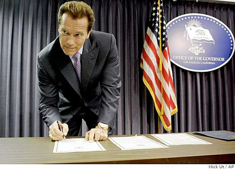 California Gov. Arnold Schwarzenegger signs declarations at a news conference in his Los Angeles office. Schwarzenegger declared a fiscal emergency and called lawmakers into a special session to address California's $11.2 billion budget deficit. Photo: Nick Ut, AP