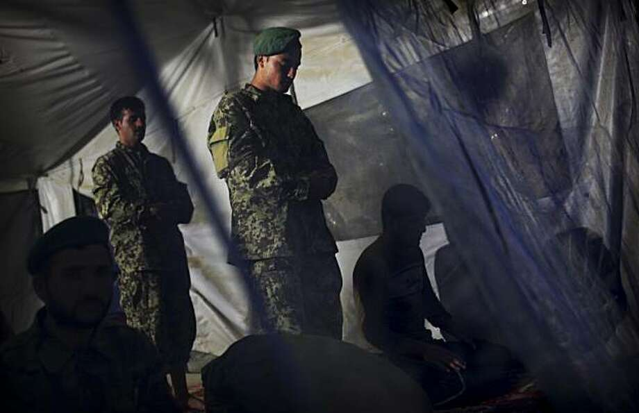 ** ADDS DATE **Afghan National Army soldiers pray in a tent during evening prayers at Combat Outpost Ware, which they share with United States soldiers from Bravo Company, 2nd Battalion of the 508 Parachute Infantry Regiment of the 82nd Airborne, in the volatile Arghandab Valley, outside Kandahar City Sunday July 11, 2010. Photo: Kevin Frayer, AP