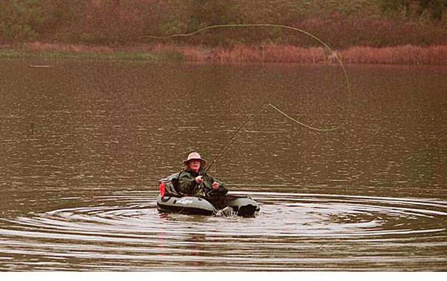 OUT THERE1/C/06JAN95/CD/Michael Maloney Josette Woolley of Fly Fishing Outfitters (flyfishing store in SF and Lafayette) casts a line from a float tube at Lafayette Reservoir. More women are getting involved in the sport.