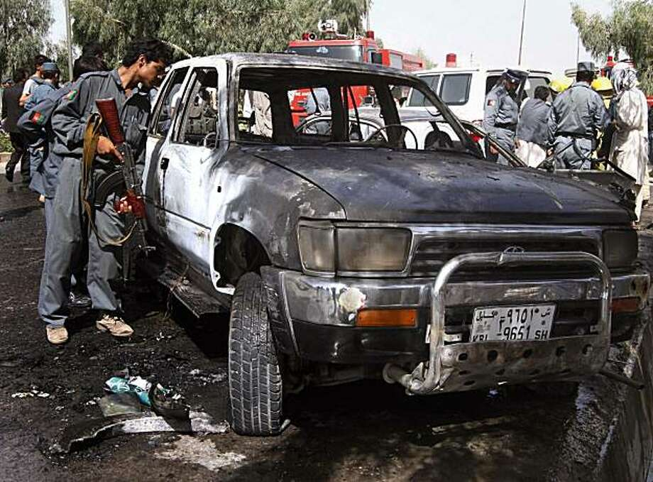 An Afghan policeman inspects a damaged vehicle at the scene of an explosion in Kandahar south of Kabul, Afghanistan on Saturday, July 10, 2010. One bystander was killed when the bomb, concealed in a parked motorcycle, exploded in the middle of the afternoon, said  the city's security chief. Photo: Allauddin Khan, AP