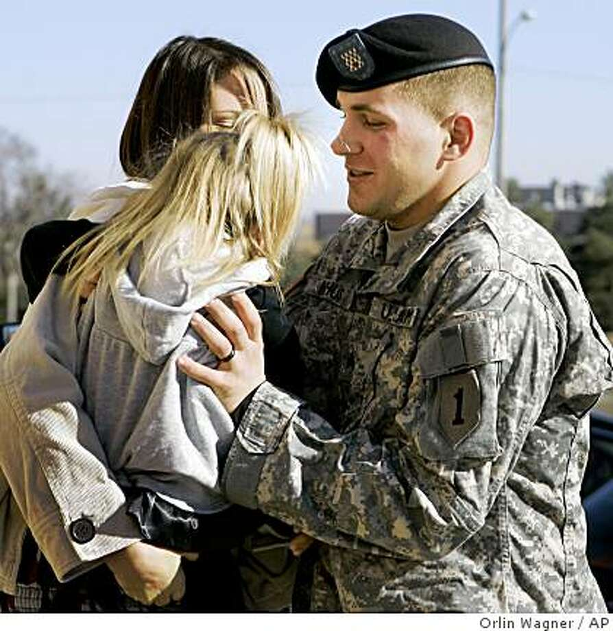 ** CORRECTS SPELLING OF RYAN ** Sgt, Ryan Nyhus reaches for his daughter Caidence before he re-enlists during a ceremony at Fort Riley, Kan., Wednesday, Nov. 26, 2008. Nyhus' wife Ashley is holding Caidence. (AP Photo/Orlin Wagner) Photo: Orlin Wagner, AP