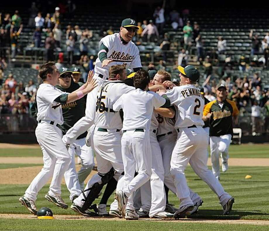 The Oakland Athletics mob pitcher Dallas Braden after his perfect game, the 19th in MLB history, against the Tampa Bay Rays in Oakland on Sunday. Photo: Carlos Avila Gonzalez, The Chronicle