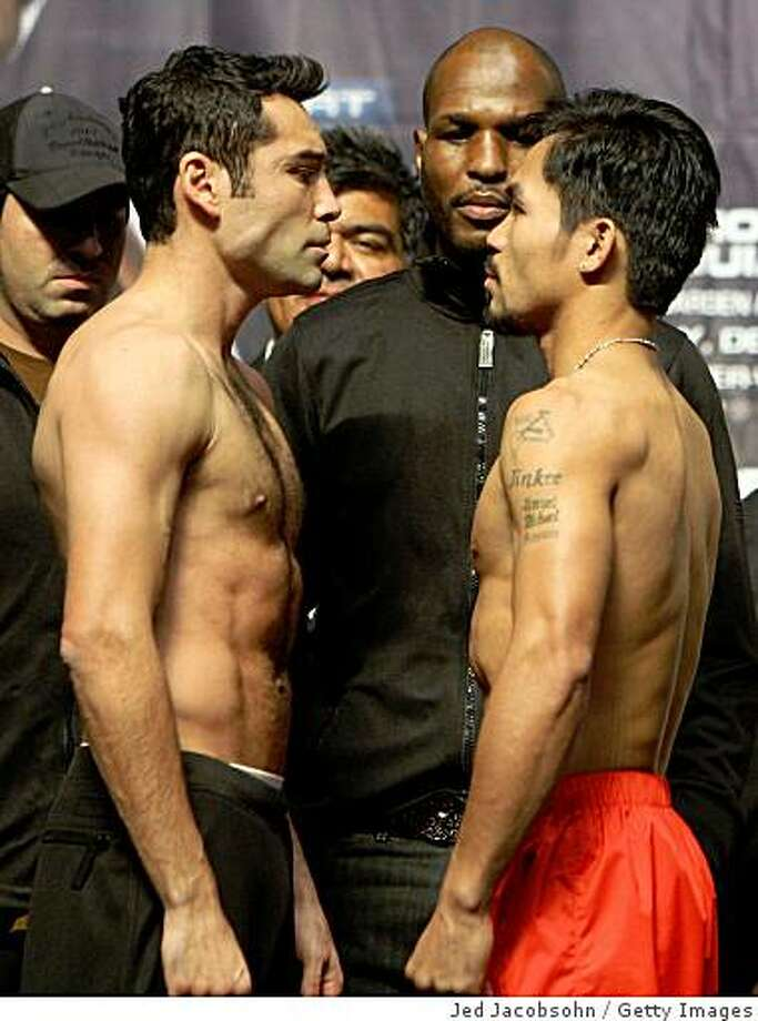 LAS VEGAS - DECEMBER 05:  (L-R) Oscar De La Hoya and Manny Pacquiao of the Philippines stand face-to-face during the weigh-in for their welterweight fight at the MGM Grand Garden Arena December 5, 2008 in Las Vegas, Nevada. De La Hoya fights Pacquiao December 6th.  (Photo by Jed Jacobsohn/Getty Images) Photo: Jed Jacobsohn, Getty Images