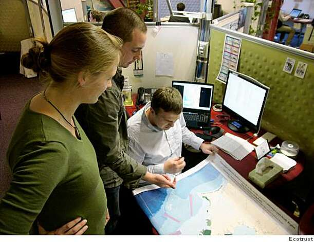 Ecotrust staffers examine GIS fishing maps of the northern California coast. From left, they are: Astrid Scholz, vice president of knowledge systems, Charles Steinback, senior GIS analyst, and Jon Bonoski, GIS analyst. Photo: Ecotrust