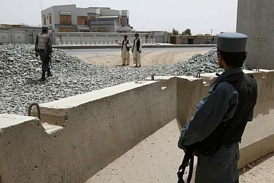 Afghan policeman stands guard at a police base which came under attack last night in Kandahar, south of Kabul, Afghanistan, Wednesday, July 14, 2010. Three U.S. troops and five Afghan civilians died in a car bomb blast and gunfire outside the base Tuesday. Photo: Allauddin Khan, AP