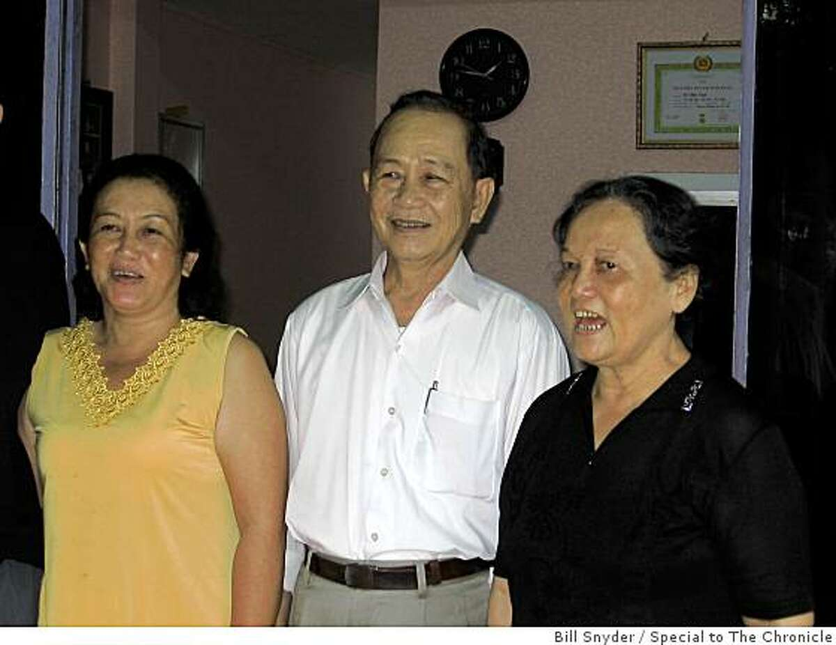 Right to Left: Mai Thi Kim, her husband, Doan Vinh, 71, a hero during the American War, and their eldest daughter, Doan Thi Hien, at the family home in DaNang in mid-October. A framed certificate of Doan's Communist Party membership is on the wall behind them.