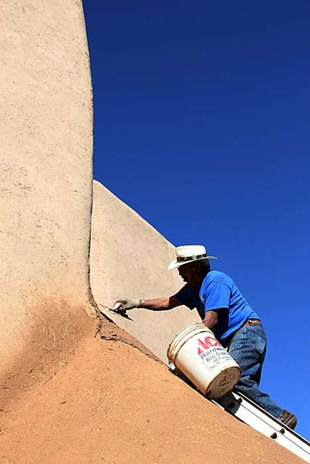In this June 14, 2010 photo, Adonio Pacheco, a parishioner of San Francisco de Asis Church in Ranchos de Taos, N.M., applies mud to the thick adobe walls of the church as part of an annual ritual that has been done for nearly 200 years. The historic church was made famous by the paintings of Georgia O'Keeffe and the photographs of Ansel Adams and Paul Strand. Photo: Susan Montoya Bryan, AP