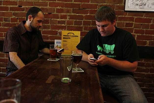 Jason Anderson and Dean Hoffman waiting out panic traffic in downtown, send text messages to loved ones at Pacific Coast Brewery after jurors convicted Johannes Mehserle on involuntary manslaughter on Thursday July, 8, 2010 in Oakland, Calif. Photo: Mike Kepka, The Chronicle