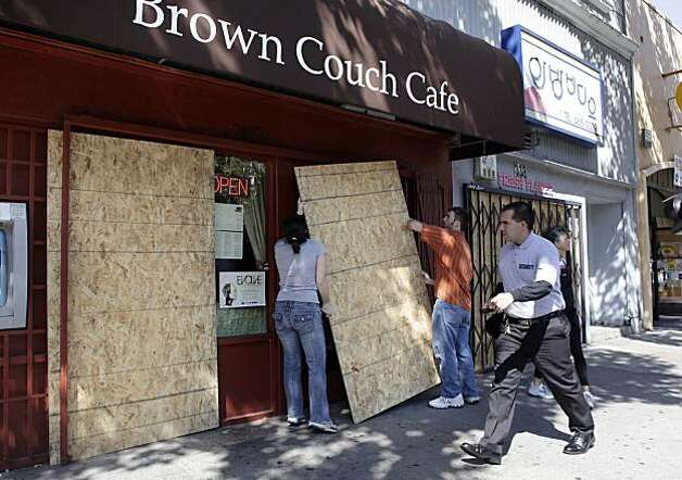 Tristen Davis, left, Kyle Ostapuk, place some sheets of plywood on the front of Brown Couch Cafe. Merchants along 14th Street in Oakland, Calif., board up their windows as the verdict in the Johannes Mehserle trial is announced on Thursday, July 8, 2010. Mehserle was convicted of involuntary manslaughter in the shooting of Oscar Grant at the Fruitvale BART station on January 1, 2009. Photo: Carlos Avila Gonzalez, The Chronicle