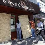 Tristen Davis, left, Kyle Ostapuk, place some sheets of plywood on the front of Brown Couch Cafe. Merchants along 14th Street in Oakland, Calif., board up their windows as the verdict in the Johannes Mehserle trial is announced on Thursday, July 8, 2010. Mehserle was convicted of involuntary manslaughter in the shooting of Oscar Grant at the Fruitvale BART station on January 1, 2009.