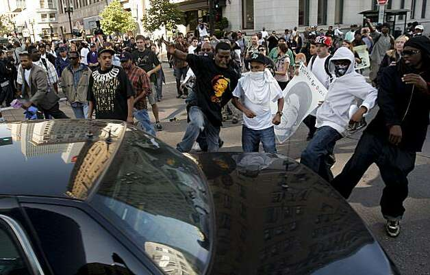 Protesters kick at an unmarked police car as it is chased out of the area of Broadway and 12th Street as groups gathered in downtown Oakland, Ca., on Thursday July 8, 2010, in support of Oscar Grant, after former BART police officer, Johannes Mehserle, was found guilty of involuntary man slaughter in the killing of Grant. Photo: Michael Macor, The Chronicle