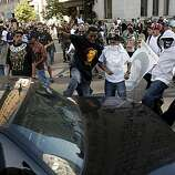 Protesters kick at an unmarked police car as it is chased out of the area of Broadway and 12th Street as groups gathered in downtown Oakland, Ca., on Thursday July 8, 2010, in support of Oscar Grant, after former BART police officer, Johannes Mehserle, was found guilty of involuntary man slaughter in the killing of Grant.