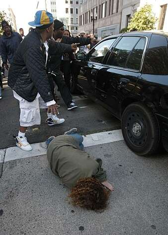 A woman is hit by an unmarked police vehicle near the corner of Broadway and 12th Street as groups gathered in downtown Oakland, Ca., on Thursday July 8, 2010, in support of Oscar Grant, after former BART police officer, Johannes Mehserle, was found guilty of involuntary man slaughter in the killing of Grant. Photo: Michael Macor, The Chronicle