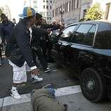 A woman is hit by an unmarked police vehicle near the corner of Broadway and 12th Street as groups gathered in downtown Oakland, Ca., on Thursday July 8, 2010, in support of Oscar Grant, after former BART police officer, Johannes Mehserle, was found guilty of involuntary man slaughter in the killing of Grant.
