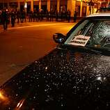 Police attempt to push back crowds after a demonstrator smashed the window of a Highway Patrol cruiser on Broadway Street following the Johannes Mehserle verdict on Thursday, July 8, 2010 in Oakland, Calif.