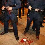 Police officers are hit with a can of red paint as they attempt to disperse crowds of demonstrators on Broadway Street  following the Johannes Mehserle verdict on Thursday, July 8, 2010 in Oakland, Calif.