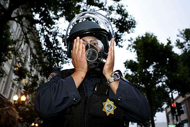 Police officers prepare for confrontation with crowds of people on Broadway Street as they put on their gas masks following the Johannes Mehserle verdict on Thursday, July 8, 2010 in Oakland, Calif. Photo: John Sebastian Russo, The Chronicle