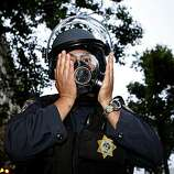 Police officers prepare for confrontation with crowds of people on Broadway Street as they put on their gas masks following the Johannes Mehserle verdict on Thursday, July 8, 2010 in Oakland, Calif.