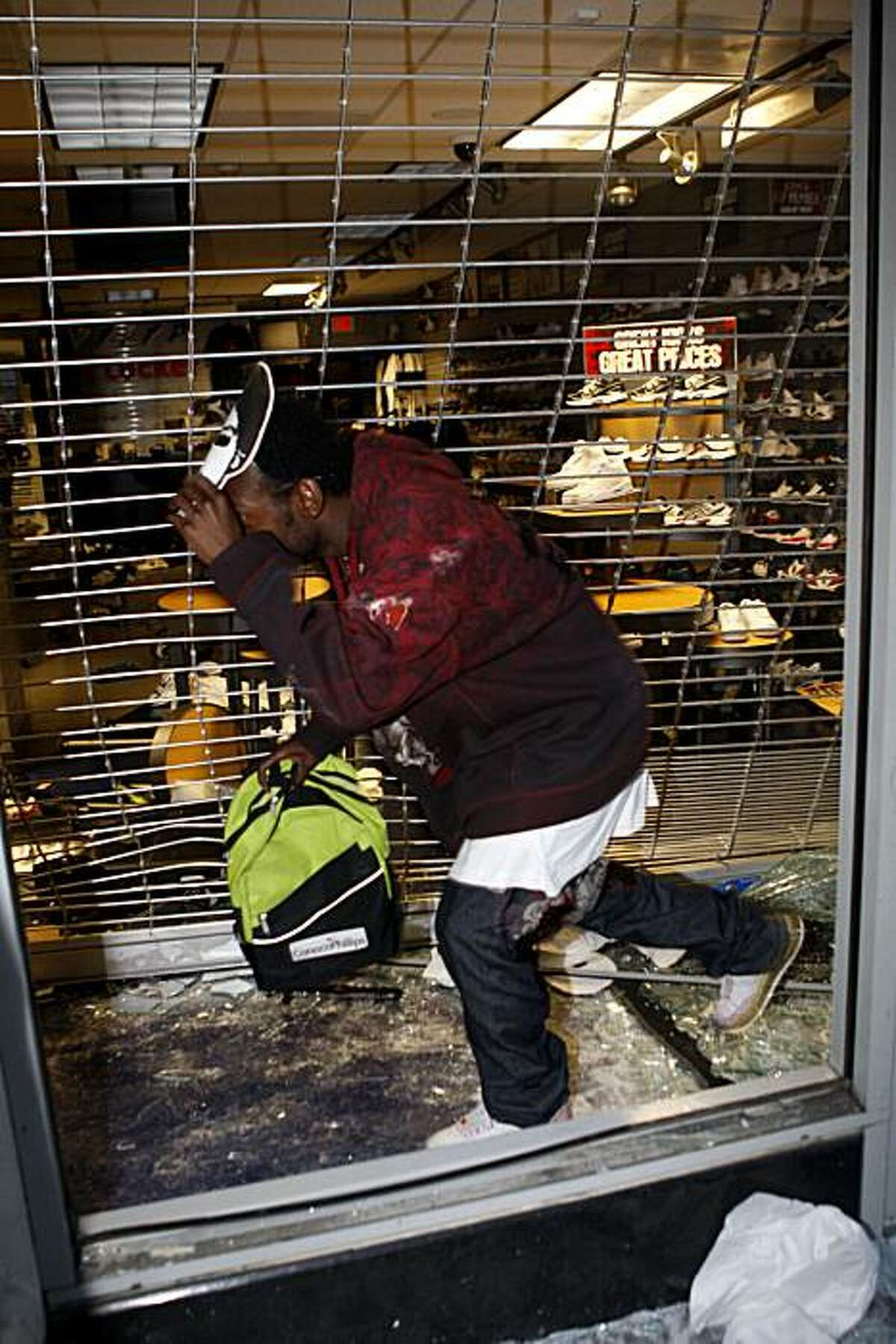 Looters break into and rush out of a Foot Locker steeling shoes and clothing on Broadway Street following the Johannes Mehserle verdict on Thursday, July 8, 2010 in Oakland, Calif.