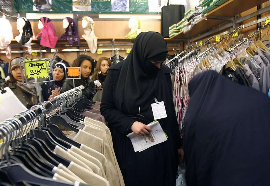FILE - This April 4, 2010 file photo shows women in Islamic face-covering veils looking at clothes inside an exhibition hall during the 27th annual meeting of French Muslims, in Le Bourget, outside Paris. France's lower house of parliament has approved aban on burqa-like Islamic veils Tuesday July 13, 3010, a move that is popular among French voters despite serious concerns from Muslim groups and human rights advocates. Photo: Christophe Ena, Associated Press