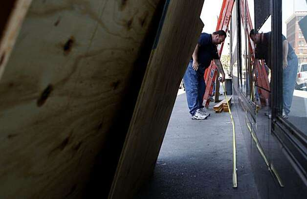 Ron Lewis, an employee of General Contractor JH Bryant of Hayward, measures for plywood installation Friday at Sears on Telegraph, where vandals broke storefront windows following the the Johannes Mehserle conviction on Thursday. Photo: John Sebastian Russo, The Chronicle