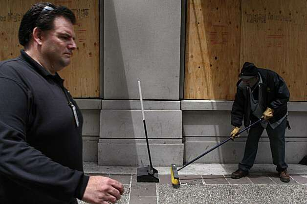 City worker Kenneth York sweeps up broken glass from windows of the Far East National Bank on Broadway on Friday after demonstrators vandalized business storefronts following the Johannes Mehserle conviction on Thursday in Oakland. Photo: John Sebastian Russo, The Chronicle