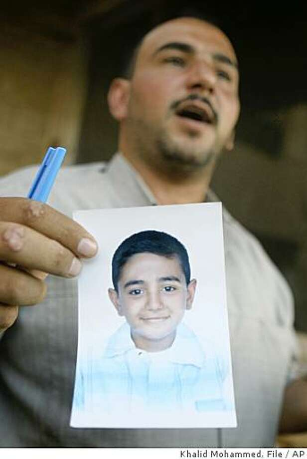 ** FILE ** In this Oct. 4, 20007, file photo Mohammed Hafiz, 37, holds a picture of his late 10-year-old son, Ali Mohammed, in his Baghdad home as he describes how he died after the Sept. 16 attack by the Blackwater USA contractors in Baghdad.  Security contractor Blackwater Worldwide, which an angry Iraqi government blames for the shooting deaths of 17 civilians in the incedent, is not expected to face criminal charges, all but ensuring the company will keep its multimillion dollar contract to protect U.S. diplomats, according to people close to the investigation. (AP Photo/Khalid Mohammed/File) Photo: Khalid Mohammed, File, AP