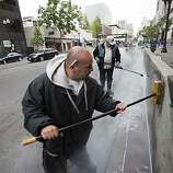 Oakland City workers Luis Coral (L) and Antonio Vasquez clean up the aftermath of a protest in downtown Oakland over the involuntary manslaughter conviction of former BART police officer Johannes Mehserle for the shooting death of Oscar Grant, July 9, 2010 in Oakland, California.  Photograph by David Paul Morris/Special to the Chronicle
