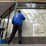 Ron Gooden, an employee of Peralta Service Corporation cleans off the window of a business during the aftermath of a protest in downtown Oakland over the involuntary manslaughter conviction of former BART police officer Johannes Mehserle for the shooting death of Oscar Grant, July 9, 2010 in Oakland, California.  Photograph by David Paul Morris/Special to the Chronicle