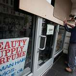 Tom Nguyen removes boards from his storefront window on Broadway as workers clean up the aftermath of a protest in downtown Oakland over the involuntary manslaughter conviction of former BART police officer Johannes Mehserle for the shooting death of Oscar Grant, July 9, 2010 in Oakland, California.  Photograph by David Paul Morris/Special to the Chronicle